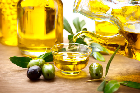 aceite de oliva: Aceite de oliva virgen verter en un cuenco de cerca Foto de archivo