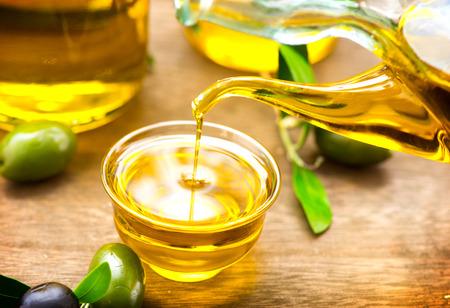 aceite oliva: Aceite de oliva virgen verter en un cuenco de cerca Foto de archivo