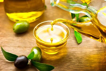 foglie ulivo: Olio d'oliva vergine che versa in una ciotola da vicino