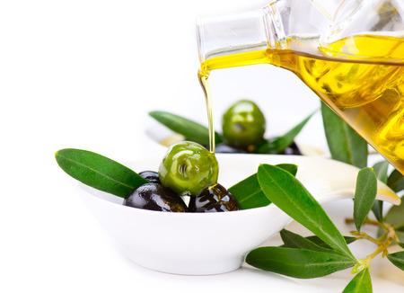 Olijfolie. Gieten vergine olijfolie op olijven Stockfoto