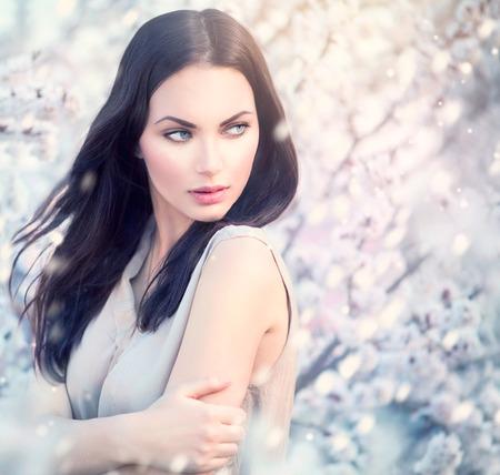 mooie brunette: Voorjaar mode meisje outdoor portret in bloeiende bomen