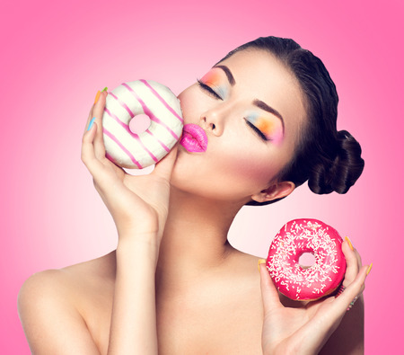 donut: Beauty fashion model girl taking colorful donuts