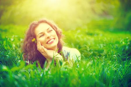 deitado: Mulher nova bonita ao ar livre apreciando a natureza