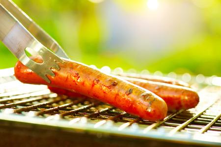 perro caliente: Salchicha a la parrilla en la parrilla en llamas. Barbacoa al aire libre. BBQ