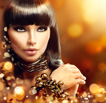 model: Fashion model brunette girl with golden accessories