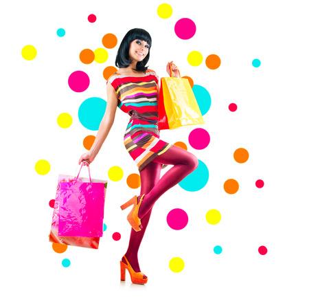 compras: Retrato de cuerpo entero de la chica de moda con bolsas de la compra en blanco