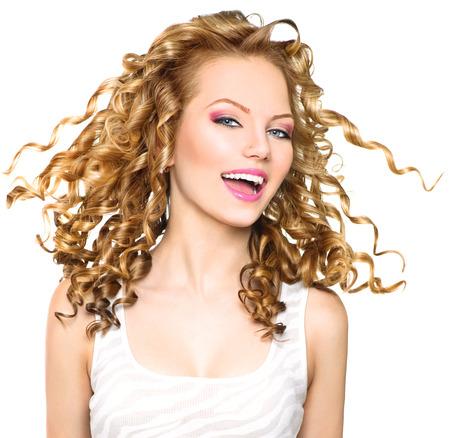 cabello: Muchacha de la belleza modelo con que sopla el pelo rizado rubio Foto de archivo