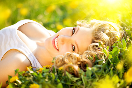 wellness environment: Beautiful young woman lying on a field enjoying nature
