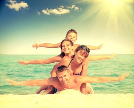 幸せな家族がビーチで楽しんで。うれしそうな家族
