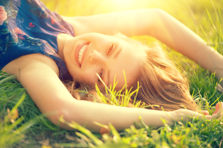 grass flower: Beautiful young woman lying on the field in green grass Stock Photo