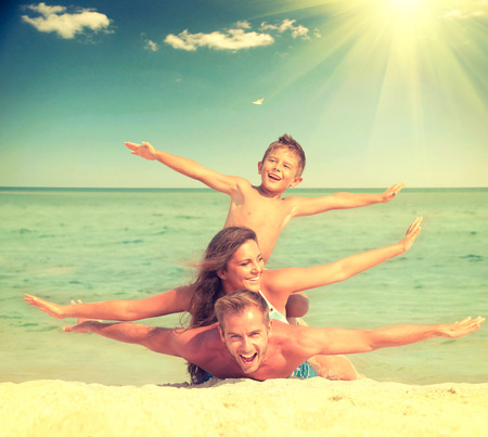 família: Família feliz se divertindo na praia. Família alegre