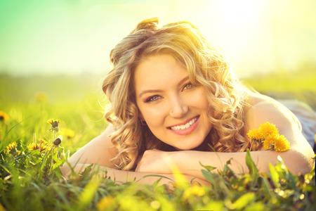 rubia: Joven y bella mujer acostado en un campo de la naturaleza disfrutando