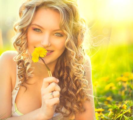 タンポポの花の臭いの美しさ金髪のモデルの少女