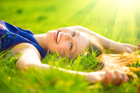 Beautiful young woman lying on the field in green grass 스톡 콘텐츠