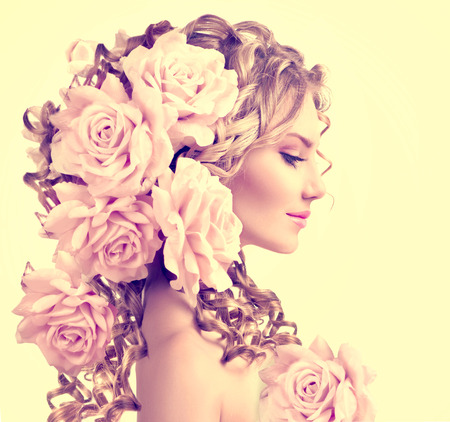 skönhet: Skönhet flicka med rosa blommor frisyr. Långt permanentat lockigt hår