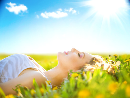 Beautiful healthy girl lying on summer field with flowers Foto de archivo
