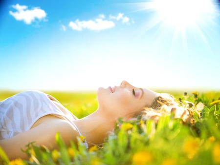 campo de flores: Hermosa niña saludable acostado en el campo de verano con flores