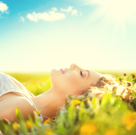 with pollen: Beautiful healthy girl lying on summer field with flowers Stock Photo