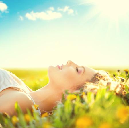 Mooie gezonde meisje liggend op zomer veld met bloemen Stockfoto