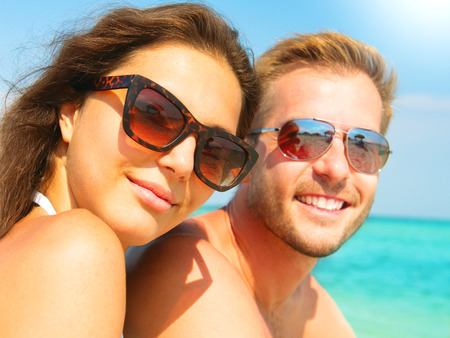 perfect teeth: Happy couple in sunglasses having fun on the beach