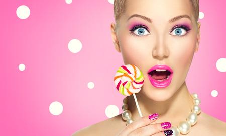Funny girl holding lollipop over pink polka dots