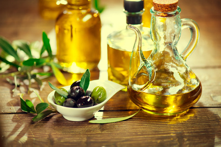 Olives and virgin olive oil on the wooden table Stock Photo - 39944255