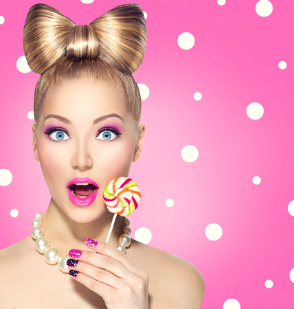 Funny girl eating lollipop over pink polka dots  Archivio Fotografico
