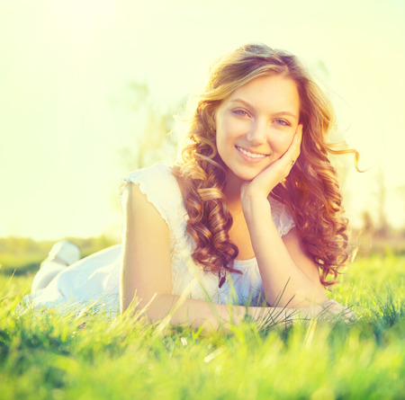 美丽浪漫的女孩躺在夏日的户外田野上