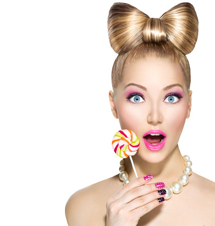 model: Funny girl with bow hairstyle eating colorful lollipop