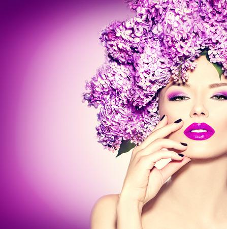 divat: Szépség divatmodell lány lila virágok frizura Stock fotó