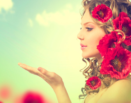 moda mujer: Muchacha de la belleza con las flores rojas de amapola peinado y las manos abiertas