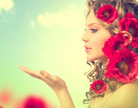 Schoonheid meisje met rode papaver bloemen kapsel en open handen Stockfoto
