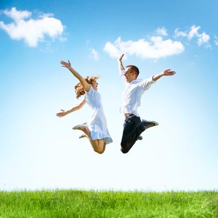 幸せなカップルの屋外。緑の野原に家族をジャンプ