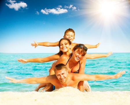 家庭: 假期。有樂趣在海灘上幸福的家庭 版權商用圖片