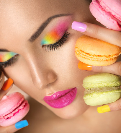 Beauty model girl taking colorful macaroons photo