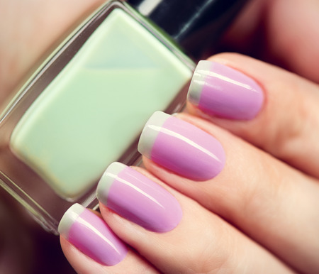 nail polish bottle: Stylish colorful nails and nailpolish bottle closeup