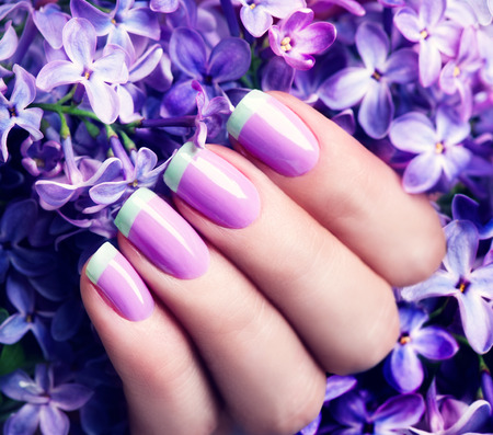 Manicured nails. Violet with green colors art manicure 스톡 콘텐츠
