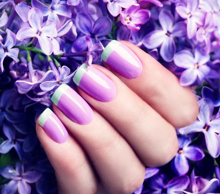 Manicured nails. Violet with green colors art manicure Foto de archivo