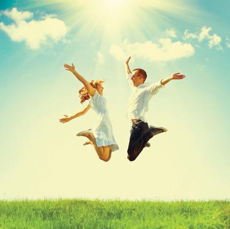 saltando: Al aire libre Pareja feliz. Saltando de la familia en el campo verde