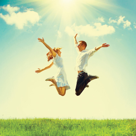 woman freedom: Happy couple outdoor. Jumping family on green field Stock Photo