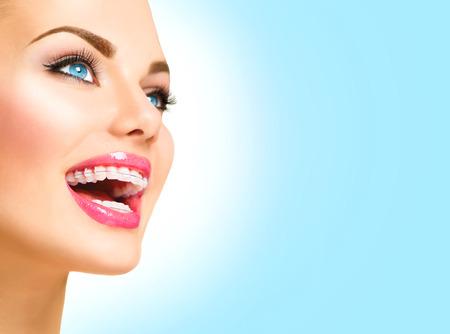 muela: Hermosa mujer sonriente. Apoyos de cer�mica del primer en los dientes