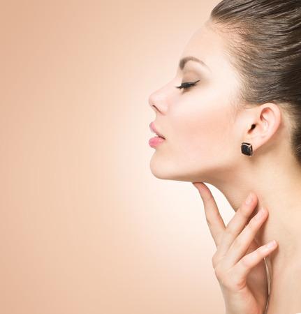 ansikten: Skönhetstående. Vackra spa kvinna röra hennes ansikte