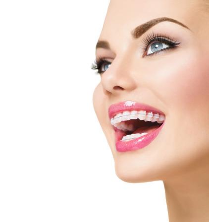 s úsměvem: Krásná žena s úsměvem. Detailní záběr keramické rovnátka na zubech Reklamní fotografie