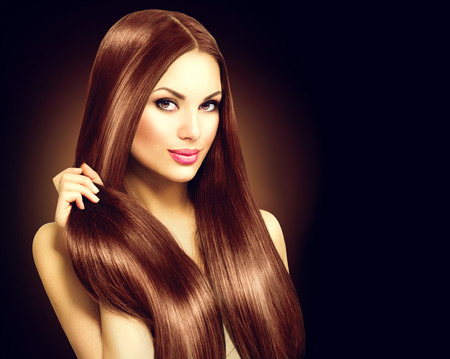 hair coloring: Beautiful brunette woman touching her long shiny straight hair Stock Photo
