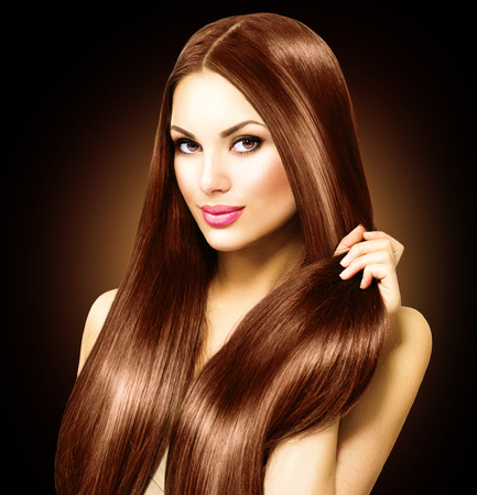 color hair: Beautiful brunette woman touching her long shiny straight hair Stock Photo
