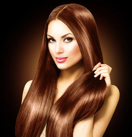 salon de belleza: Hermosa mujer morena tocar su largo pelo lacio y brillante