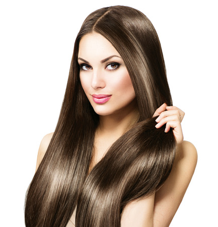 shine: Beautiful brunette woman touching her long shiny straight hair Stock Photo
