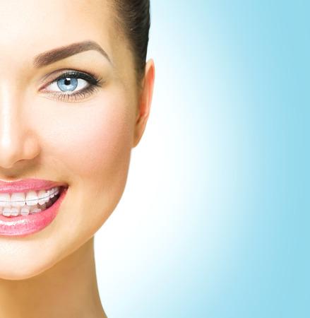 diente: Hermosa mujer sonriente. Apoyos de cer�mica del primer en los dientes