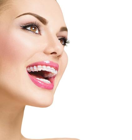 Mooie vrouw lachend. Close-up keramische beugels op de tanden