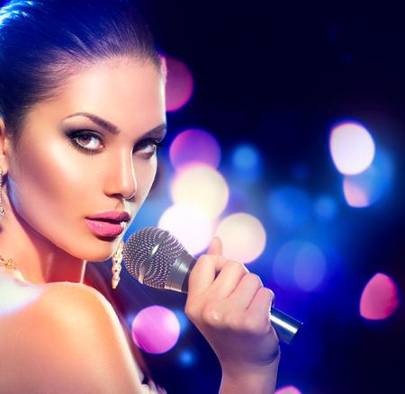 Vrouw met de microfoon over het knipperen bokeh nacht achtergrond